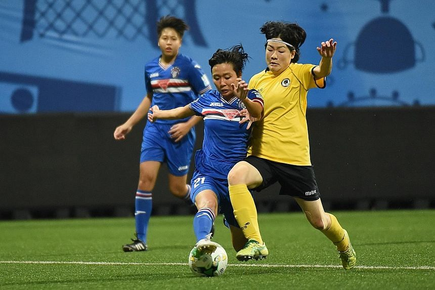 Warriors FC's Nur Izyani and Tanjong Pagar's Yuki Monden tussling for the ball during the Football Association of Singapore (FAS) Women's Challenge Cup final at Jalan Besar Stadium yesterday. Warriors retained their title with a 6-0 victory. In the t