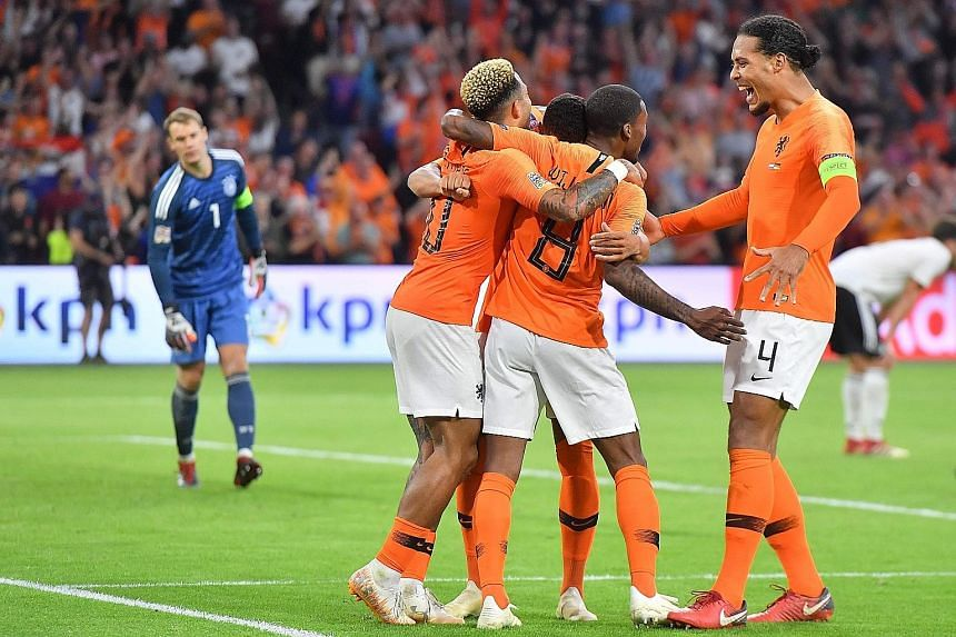 The Netherlands' players celebrating after midfielder Georginio Wijnaldum (No. 8) scores late into stoppage time to give the Oranje a 3-0 victory on Saturday, their first win against the Germans in 16 years.