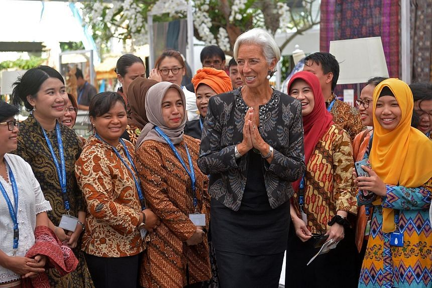 IMF managing director Christine Lagarde meeting organisers at a handicraft exhibition on the sidelines of the IMF-World Bank meetings in Bali yesterday. She described the meetings, which drew 36,669 delegates and other participants from all over the