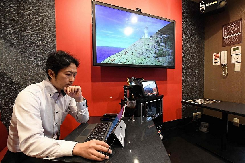 The Japanese salaryman is never short of a place to work in, whether it is inside camping tents on a lawn (above) outside a Tokyo office building or, in the case of NTT Communications staff Hideyuki Aoki, in a rented soundproof room at a karaoke outl