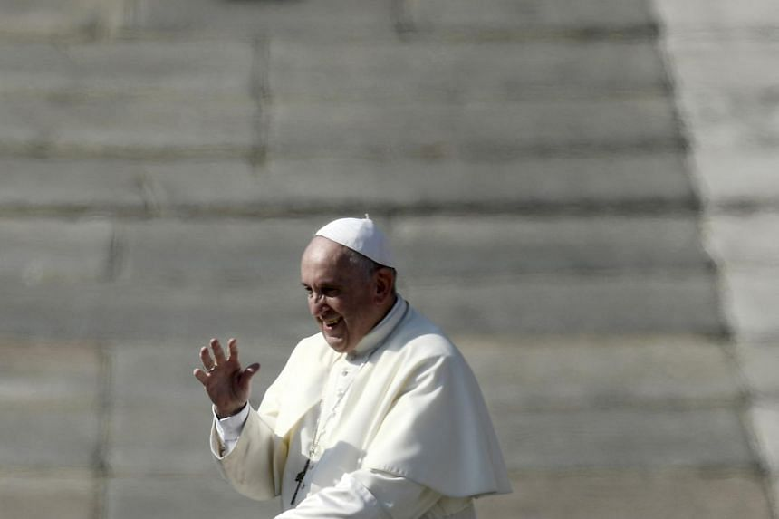 Pope Francis waves to the faithful in St Peter's Square at the Vatican, on Oct 14, 2018.
