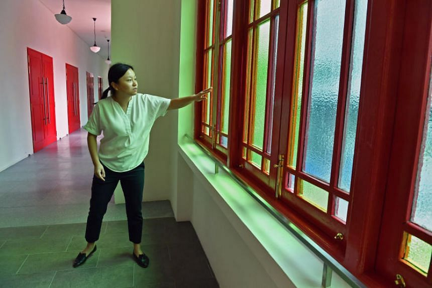 Project architect Ng Xinying explains how the paint was scrapped off the old window panes during the revamp of Stamford Arts Centre in order to restore them to its full glory.