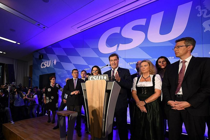 (From right) AfD's MP Stephan Protschka, co-leader Alice Weidel and vice-leader of the AfD party in Bavaria Katrin Ebner-Steiner at an election party in Mamming in southern Germany on Sunday. Bavarian Prime Minister Markus Soeder addressing supporter