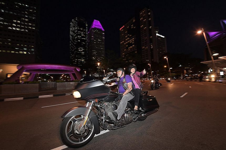 A Harley-Davidson staff member and his pillion rider Wan Wai Yee, who is visually impaired, enjoying their ride around the Suntec City Fountain of Wealth last night.
