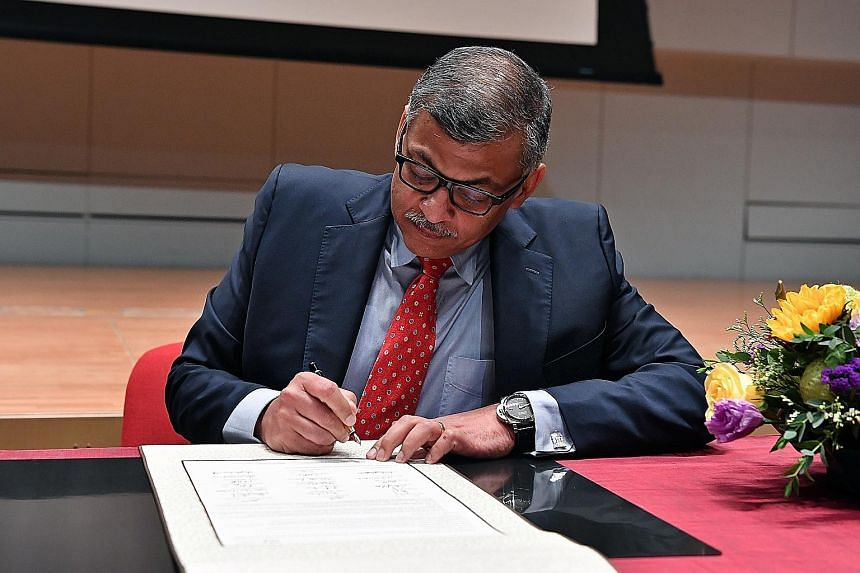 Chief Justice Sundaresh Menon signing the pledge as a witness at the Supreme Court yesterday.