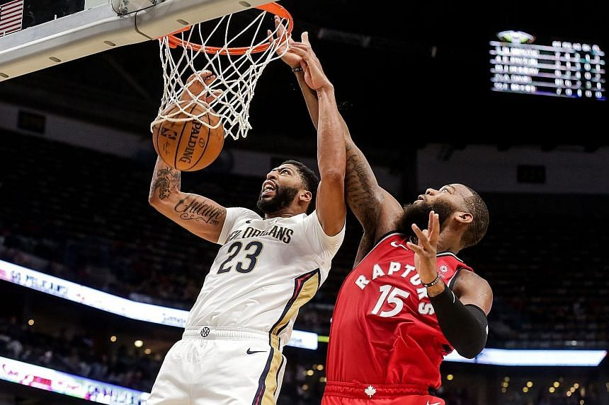 New Orleans forward Anthony Davis dunking over Toronto centre Greg Monroe in last week's pre-season game at the Smoothie King Centre.