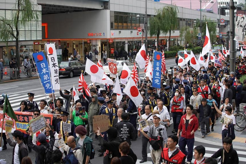 Demonstrators hold flags and placards as they march past counter-protesters during a rally against Japan Prime Minister Shinzo Abe's proposed legislation regarding foreign workers in Tokyo, on Oct 14, 2018.