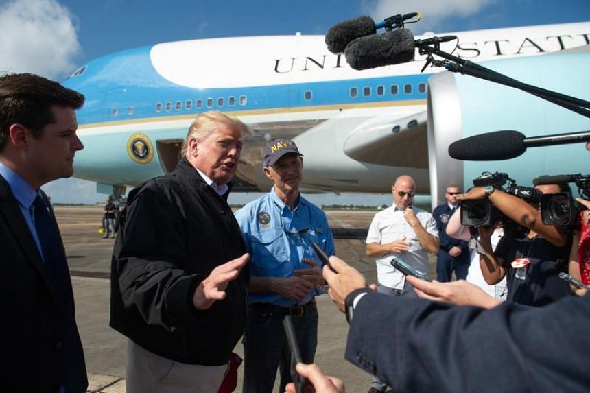 US President Donald Trump and Florida Governor Rick Scott speak to the media next to Air Force One upon Trump's arrival at Eglin Air Force Base in Florida, Oct 15, 2018, as they travel to view damage from Hurricane Michael.