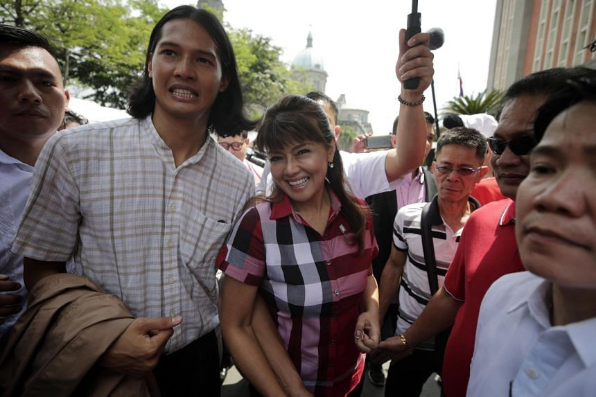 Imee Marcos (centre), daughter of former strongman Ferdinand Marcos, and her son Borgie (second from left) enter the Commission on Elections office in Manila, on Oct 16, 2018.