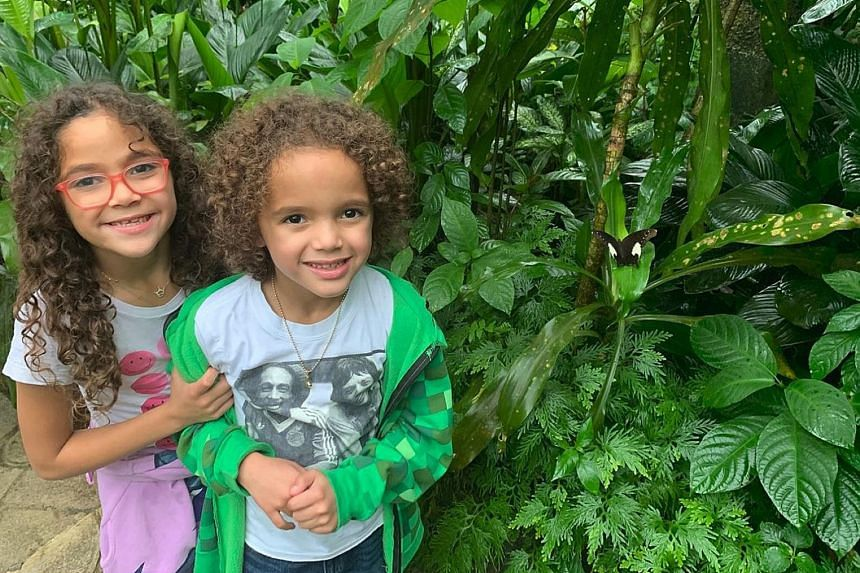 """Mariah Carey with the Petronas Twin Towers in KL behind her. Mariah Carey's twins Monroe Cannon (left) and Moroccan Scott are seen in a photo on Twitter with the caption """"at the butterfly conservatory in Kuala Lumpur""""."""