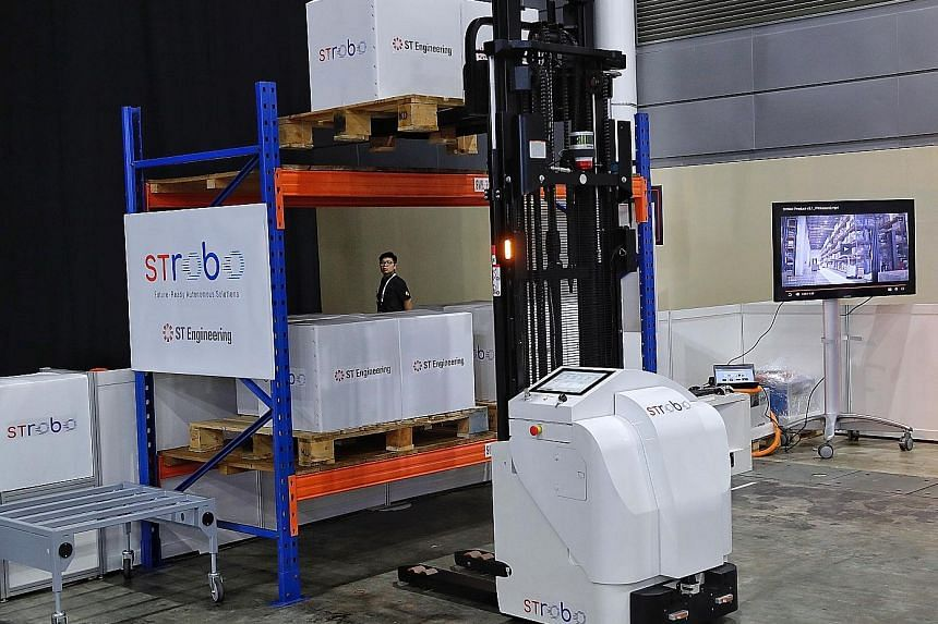 Above: ST Engineering's range of STrobo robots includes (from left) an autonomous forklift, an autonomous tow tractor and an autonomous pallet truck. Above left: The autonomous pallet stacker demonstrating its capabilities yesterday at the Industrial