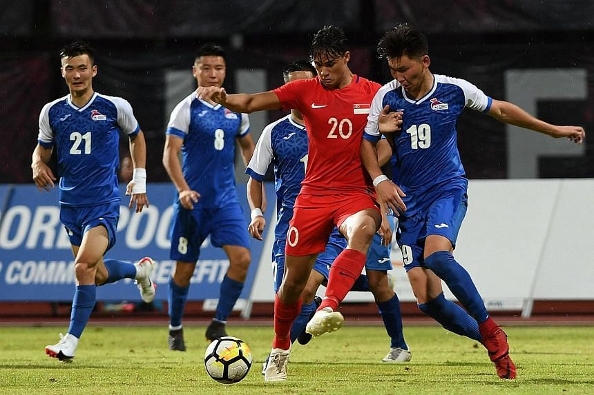 Ikhsan Fandi fending off the attention of Mongolia's Tsagaantsooj Munkh-Erdene during the Lions' 2-0 friendly win at Bishan Stadium last week. The striker netted the winner against Cambodia last night for their third victory in a row under coach Fand