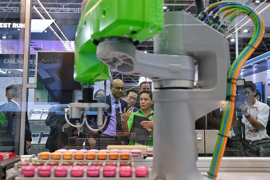 Deputy Prime Minister Tharman Shanmugaratnam observing an automated macaron-making machine during his tour of the Industrial Transformation Asia-Pacific trade show yesterday. (From left) Moderator Christoph Schmitz, Minister for Trade and Industry Ch