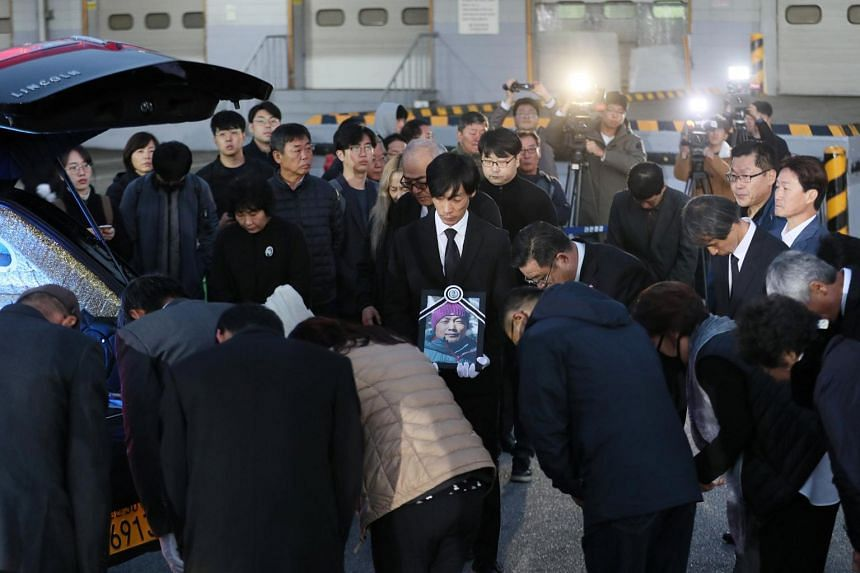 Family members and relatives bow to a coffin carrying a body of one of the five South Korean climbers who were killed in the Himalayas, at Incheon International Airport, on Oct 17, 2018.
