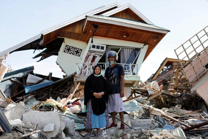 Ms Darmi and her brother Rusli stand outside her destroyed house as they look for clothes and other belongings in the rubble, in the Balaroa neighbourhood, on Oct 10, 2018.