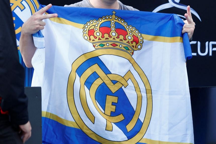 File photo showing a fan holding a Real Madrid flag at an event, on Aug 15, 2018.
