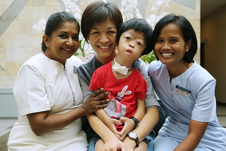 Ms Lee Seu Hong and her daughter Kang En Ning with KKH's assistant nurse clinician Selvi Thevathas and nurse clinician Maryani Abdul Wahab. Ms Lee stopped working in advertising to care for her daughter, who has Antley Bixler syndrome.