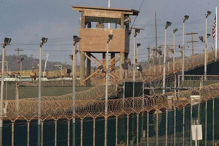Above: A watch tower at Camp Delta at the US military-run detention centre in Guantanamo Bay, Cuba. Left: Detainees performing their morning prayers at the prison. Guantanamo has not received any new inmates since 2008, and 40 remain.