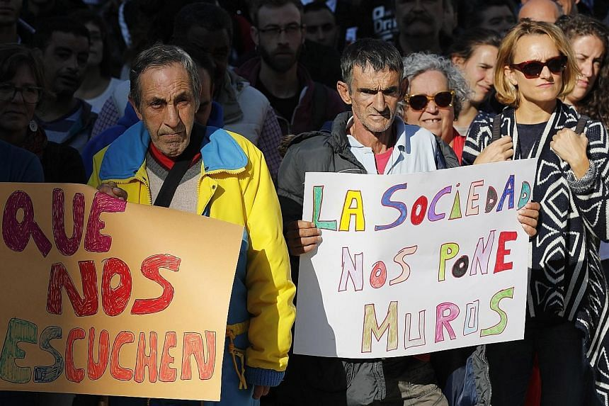"""Protesters holding banners that say """"Listen to us"""" and """"Society places walls before us"""" at a demonstration during the International Day for the Eradication of Poverty in Bilbao, Spain, yesterday."""