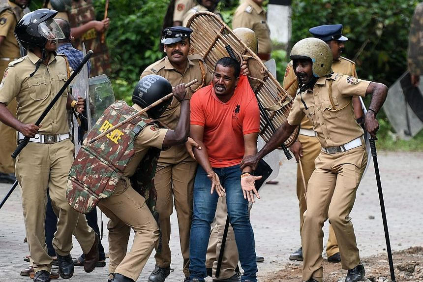 Indian police detaining an activist as protesters rallied against a Supreme Court verdict revoking a ban on the entry of women of menstrual age to a Hindu temple in the state of Kerala yesterday.