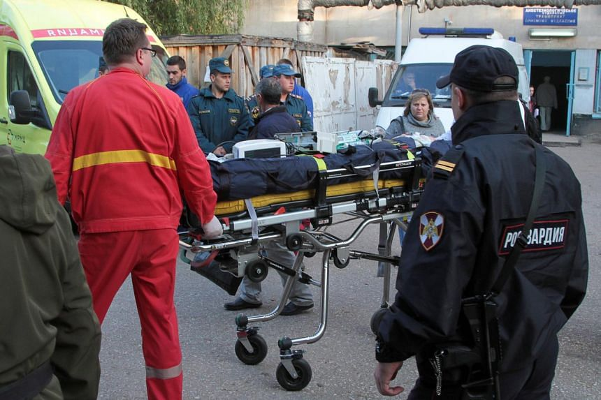 Medics transport injured people outside a hospital following an attack on a local college in the city of Kerch, Crimea, on Oct 18, 2018.