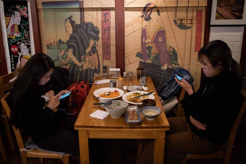 Women use their smartphones as they have dinner in a restaurant in Beijing. China has been developing homegrown innovation, but still relies on foreign technology in areas such as semiconductors.