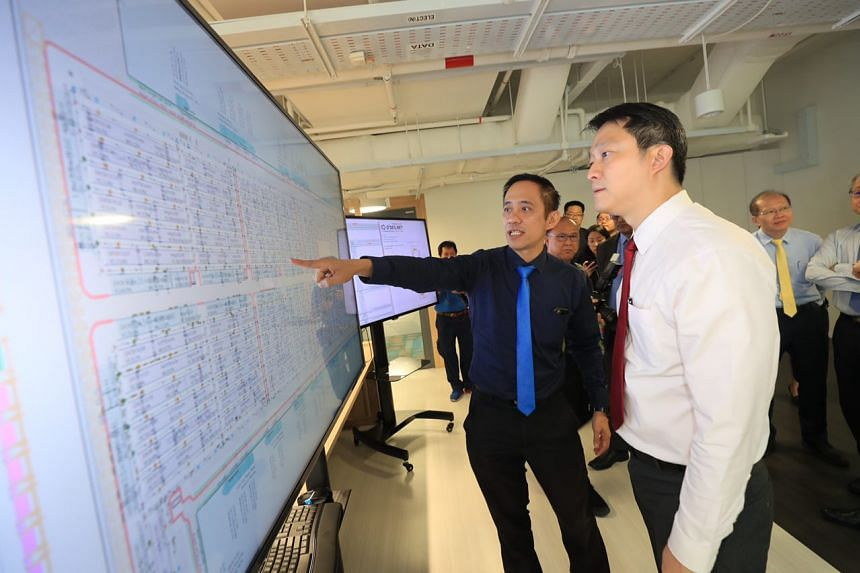 Associate Professor Lee Loo Hay (left), co-director of C4NGP, shows project presentations to Dr Lam Pin Min, Senior Minister of State for Transport and Health, at the centre.