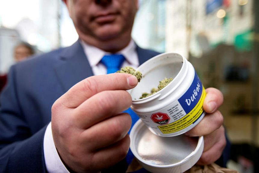 A man shows off his cannabis purchase outside the Quebec Cannabis Society store in Montreal on Oct 17, the day Canada legalised recreational marijuana.