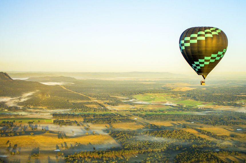 A hot air balloon flying over the Hunter Valley Region. PHOTO: DESTINATION NSW