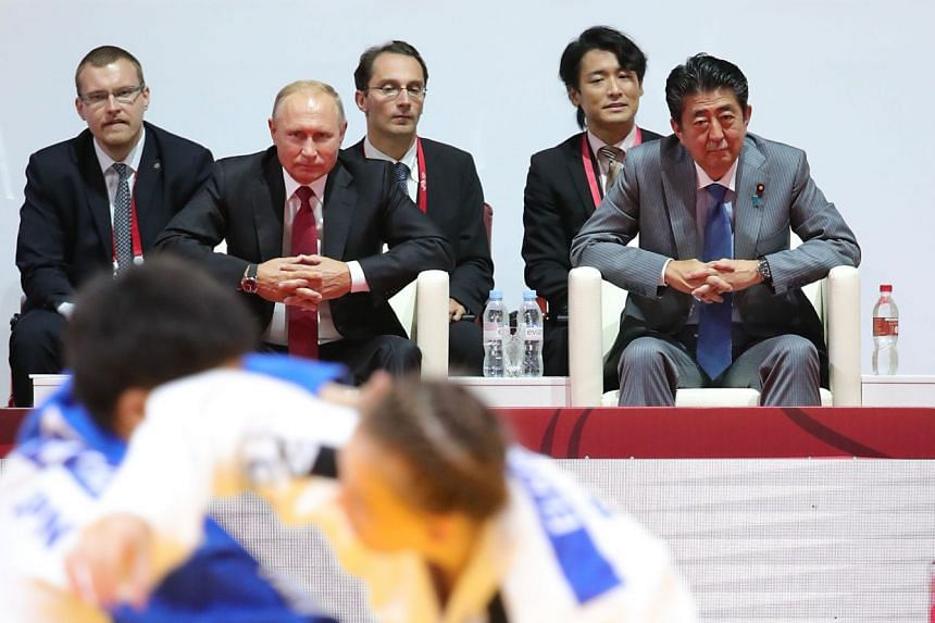 Putin (second left) and Abe (far right) attending a judo tournament in Vladivostok in September 2018.