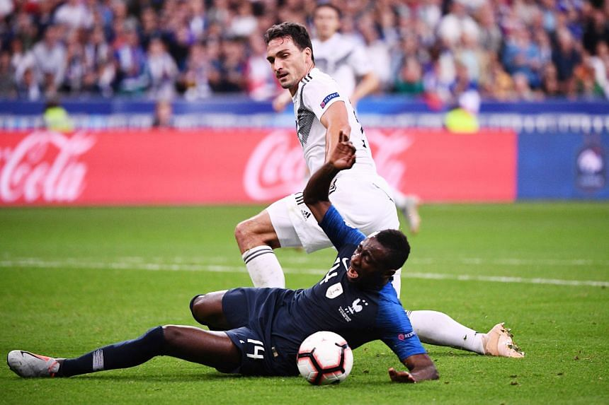 France's midfielder Blaise Matuidi going to ground in the box under a challenge from Germany defender Mats Hummels, which led to a penalty awarded to the hosts. Antoine Griezmann's conversion from the spot gave the world champions a 2-1 win in Paris