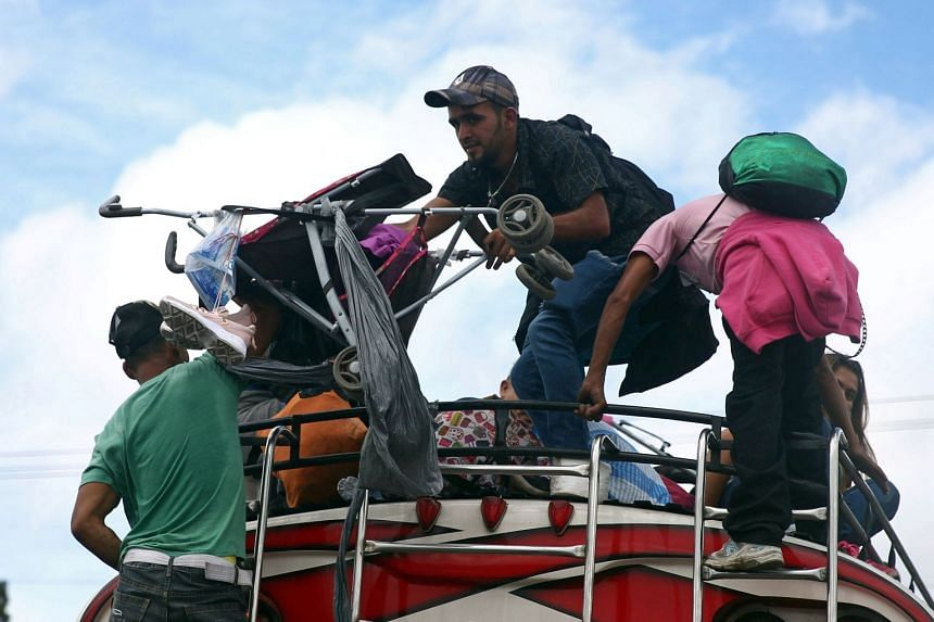 Honduran migrants, part of the caravan trying to reach the US, climb on a bus during a new leg of their travel.