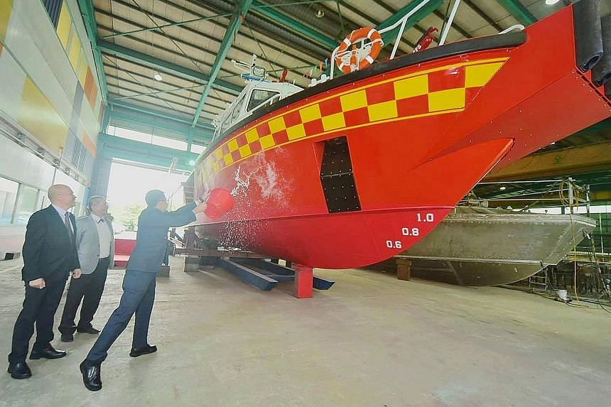 SCDF Commissioner Eric Yap launching the White Swordfish on Wednesday by splashing a bucket of sea water onto the bow. To be deployed at the upcoming Punggol marine outpost, the new vessel is the SCDF's third purpose-built Rapid Response Fire Vessel.