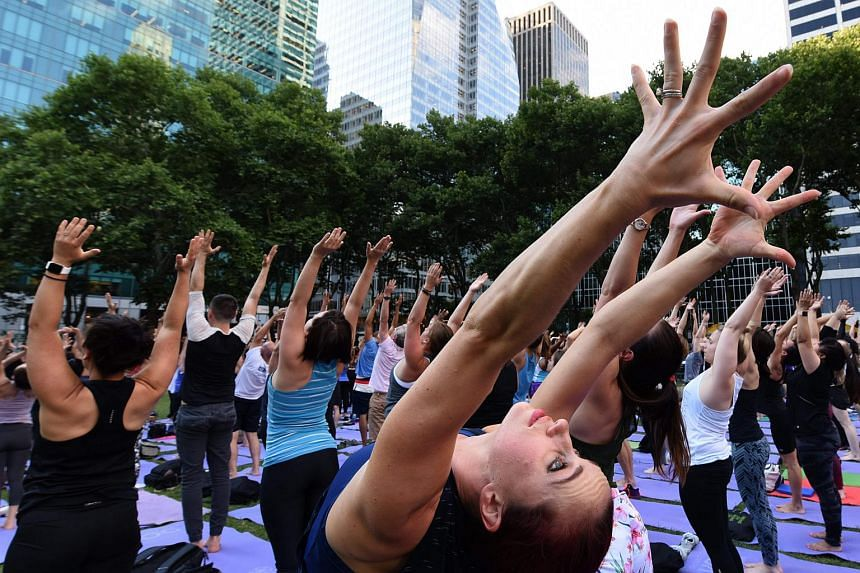 People participate in a free outdoor yoga event in Bryant Park in New York City on July 12, 2018. Women's workout leggings costing as little as 76 cents will not be available once US pulls out of the postal treaty.
