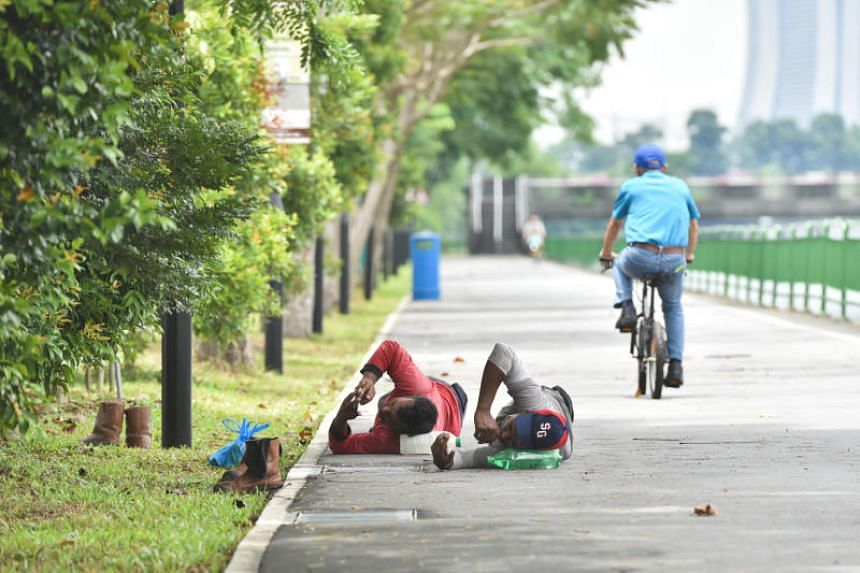 Foreign workers rest on a park connector along Geylang River on Oct 12, 2018.