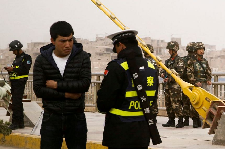 File photo of a police officer checking the identity card of a man as security forces keep watch in a street in Xinjiang.