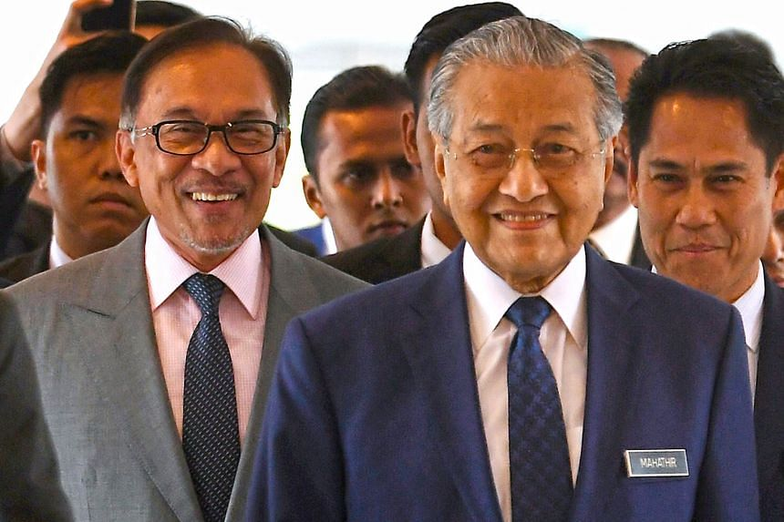 Prime Minister Mahathir Mohamad (front) and Port Dickson MP Anwar Ibrahim arriving in Parliament yesterday, where the premier presented the mid-term review of Malaysia's five-year economic blueprint.