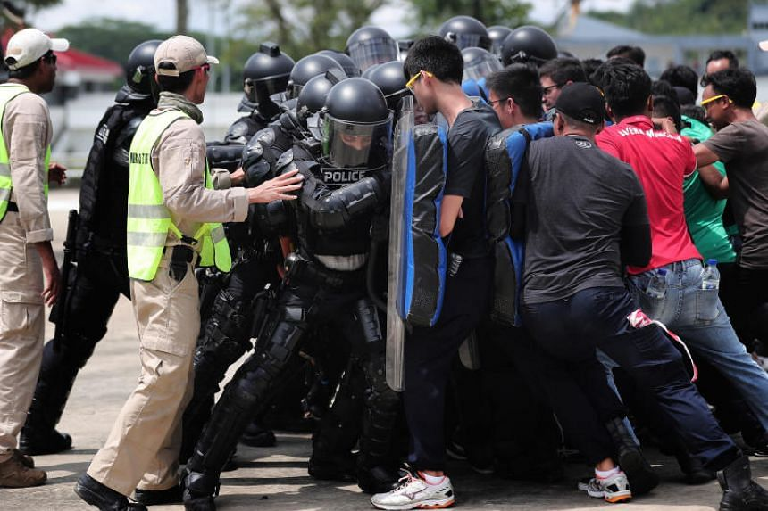 PTU officers and role-players pushing against one another during a anti-riot drill. The riot police have to stand firm as one unit and not let the rioters breach the line.