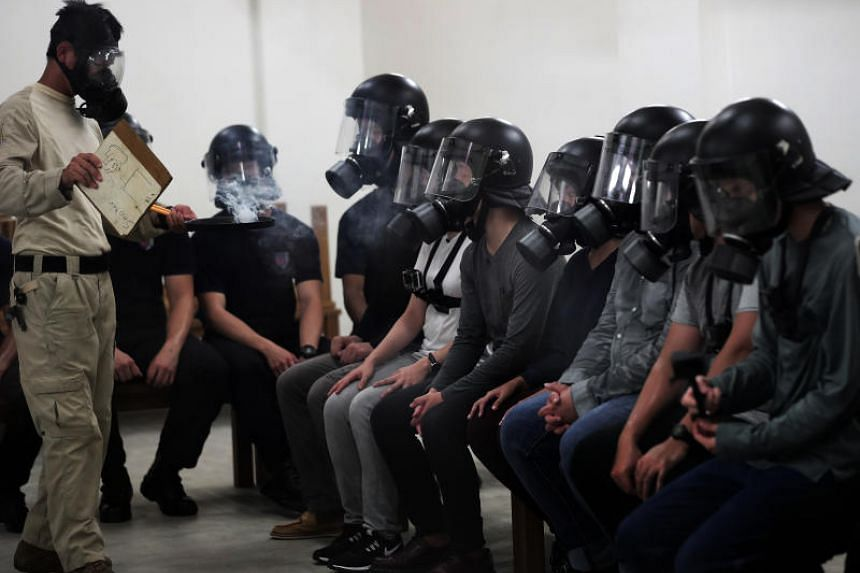 The Straits Times reporter Fabian Koh (second from right) in the tear gas chamber during a gas confidence component of the PTU training.