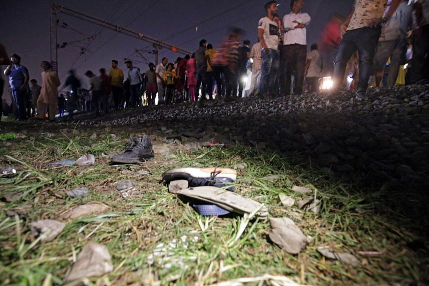 Shoes of the victims lie near the railway tracks as people gather after the accident.