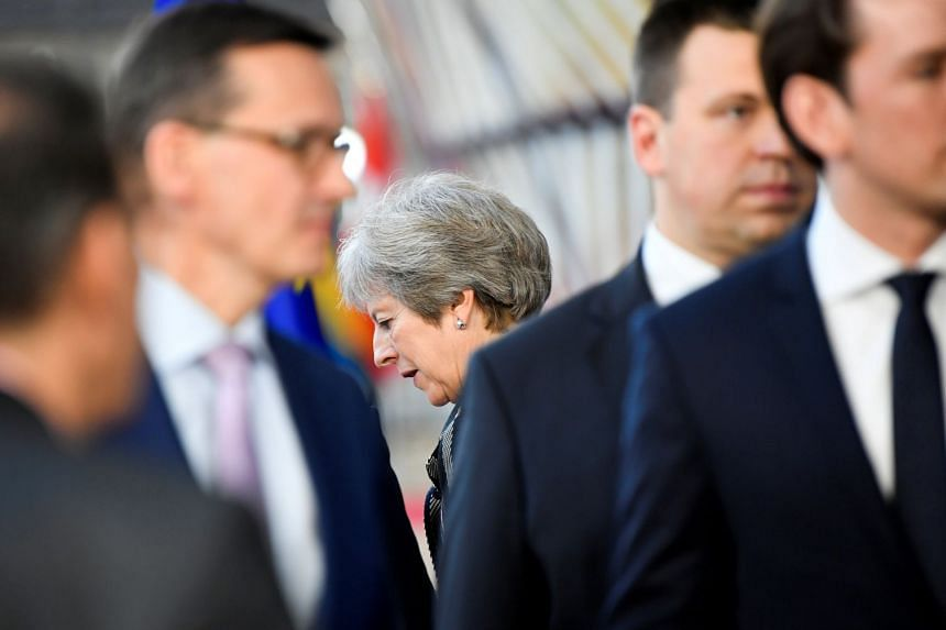 Theresa May leaves after the ASEM leaders group photo opportunity during a summit in Brussels.