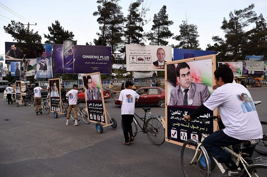 Supporters of candidate Alhaj Amir Gull Shaheen riding bicycles with a campaign trailer along a street in Kabul on Monday.