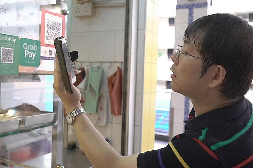Mr Chong Kwek Bin (above), who is partially blind, likes to pay for his hawker meals digitally but says it is sometimes hard to find the QR code. Mr Ng Choon Hwee (below), who is blind, has to hold his phone close to his ears when he is in a noisy en
