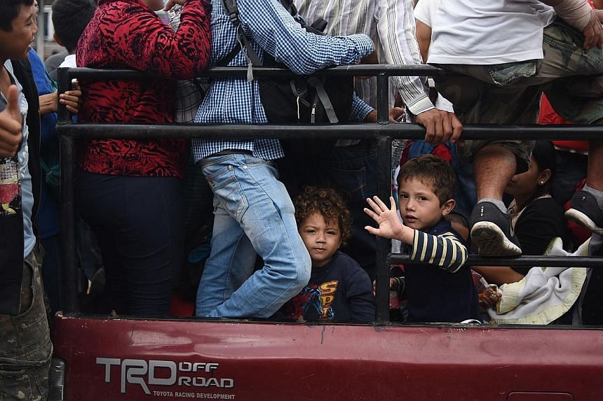 """Honduran migrants heading in a caravan towards the US, in Guatemala City, on Thursday. US President Donald Trump has threatened to send the military to close its southern border if Mexico fails to stem the """"onslaught"""" of migrants from Central America"""