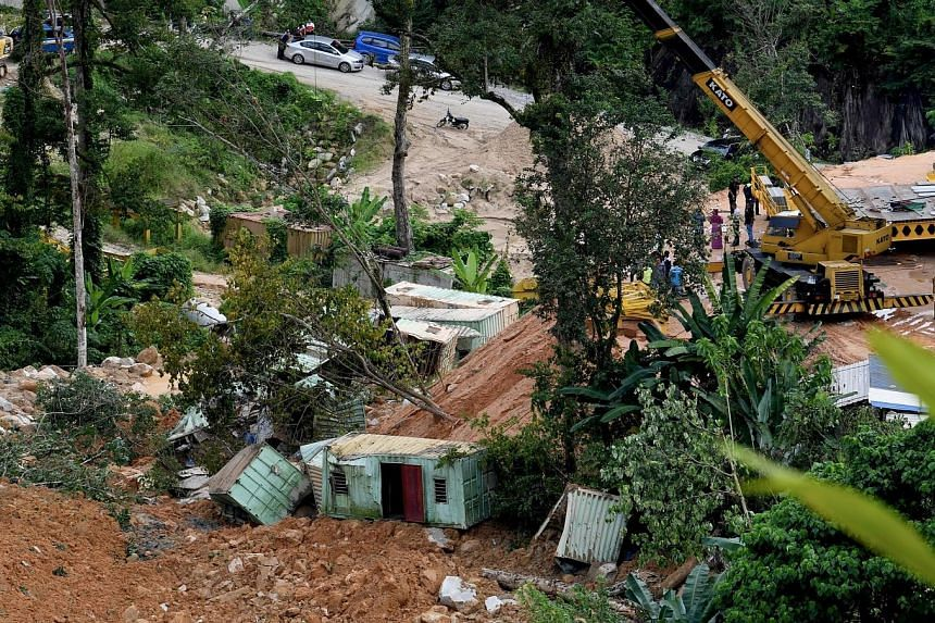 Six containers used to house workers at a construction site in Penang were brought down in a landslide yesterday, killing two and injuring one. It is feared that 10 more workers could have been buried alive.