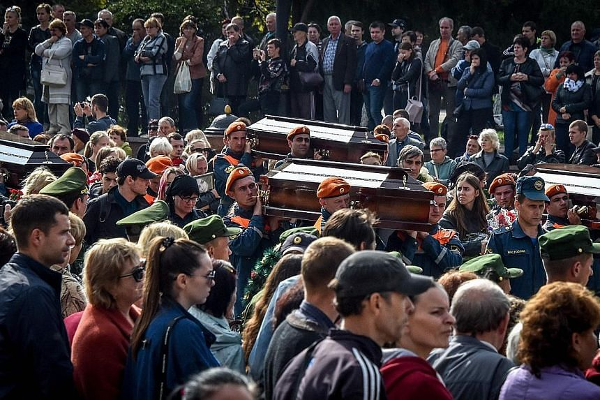 Mourners at yesterday's public funeral for victims of a school shooting in Crimea.