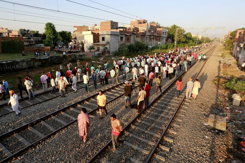 People gather at the site of an accident after a commuter train travelling at high speed ran through a crowd of people on the rail tracks in Amritsar, India, on Oct 20, 2018.