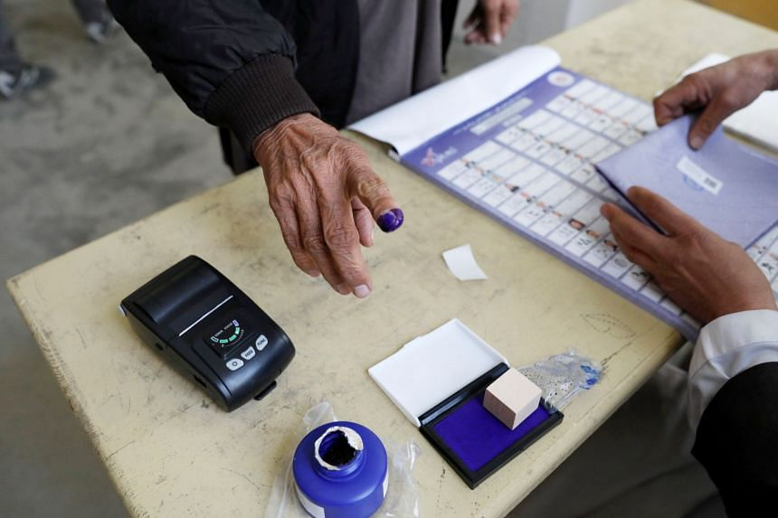 An election official assists an Afghan man at a polling station during a parliamentary election in Kabul, Afghanistan, on Oct 20, 2018.
