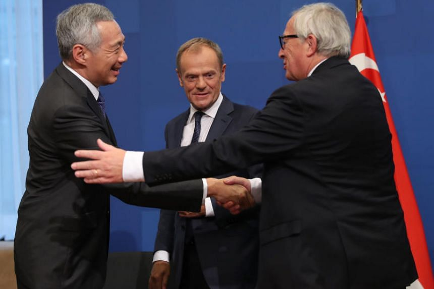 (From left) Singapore's Prime Minister Lee Hsien Loong, European Commission President Jean-Claude Juncker and European Council President Donald Tusk attend the ceremony for signing a Free Trade Agreement during the EU-ASEM summit in Brussels, Belgium