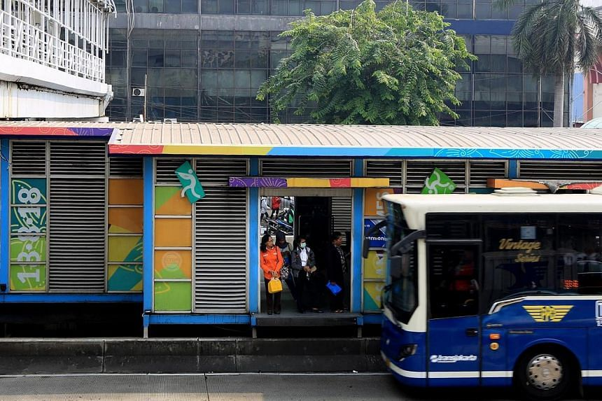 Commuters lining up at Harmoni bus stop in Central Jakarta, on July 13, 2018.